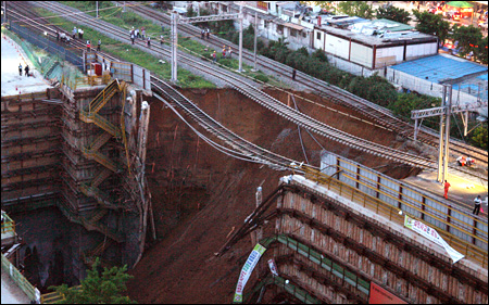 View of collapsed retaining wall with railway lines hanging in midair at building site
