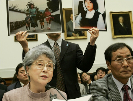 Sakie Yokota, mother of Japanese kidnap victim Megumi Yokota, testifies before a House committee on Capitol Hill in this April 27, 2006 file photo as Koh Myung-sup, a South Korean abductee, listens at right. Holding up photos of her daughter is her son Takuya Yokota. / AP-Yonhap